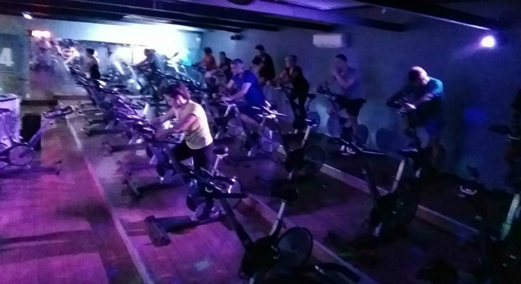 Atmosfera de boate na aula de spinning, na Cia Athletica